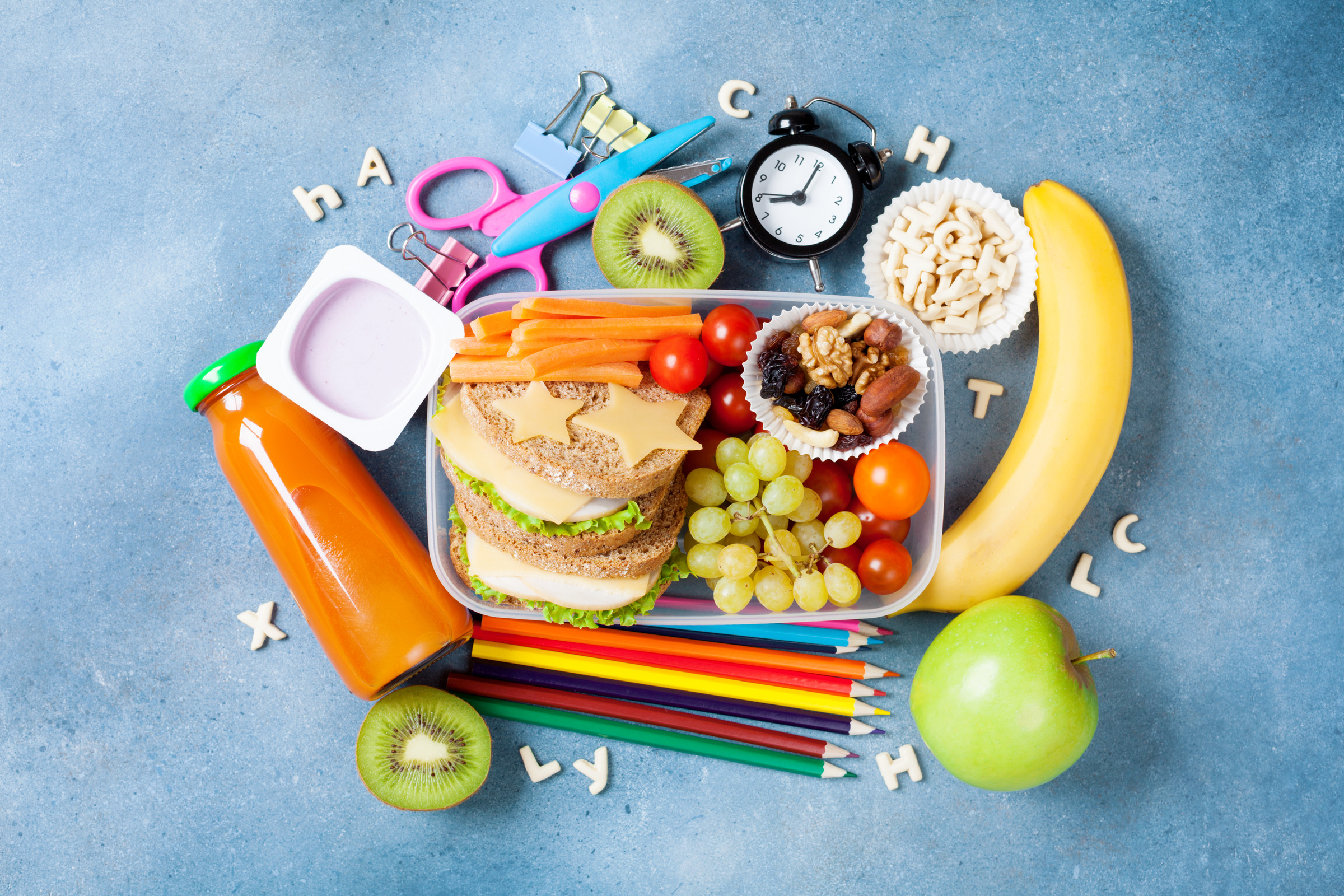 Back to school concept. Nutritional lunch box and colorful stationery top view.